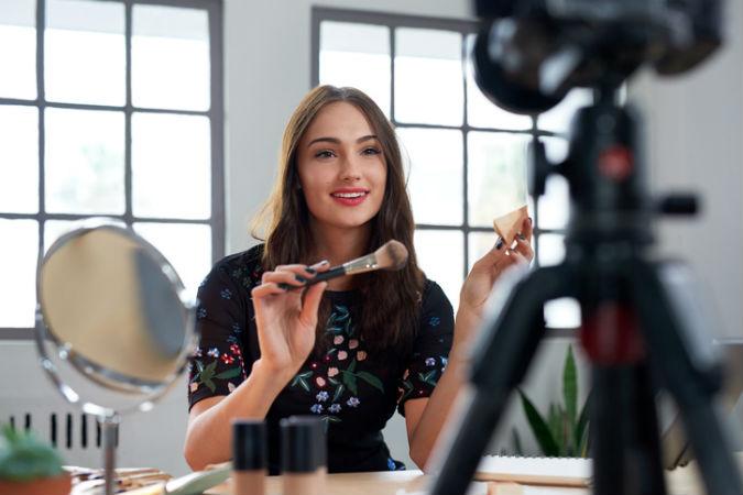 Frau schminkt sich vor einer Kamera