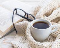 Buch, Kaffee und schwarze Brille auf liegen auf warmem Cardigan