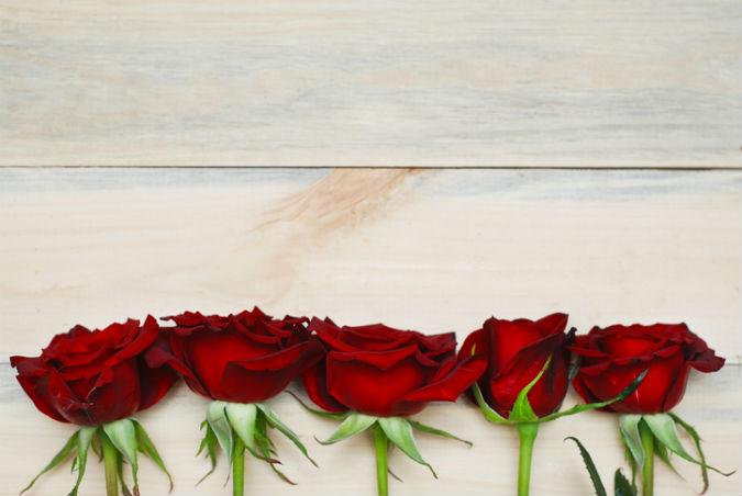 Fünf rote Rosen liegen auf einem Tisch