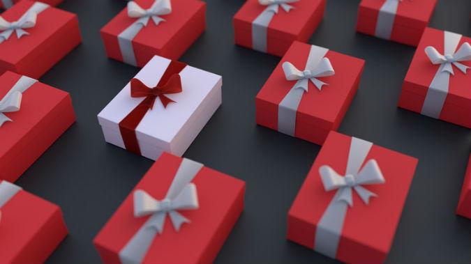 Ein Bild von roten Geschenkverpackungen aus denen ein weißes, individualisiertes Geschenk heraus sticht