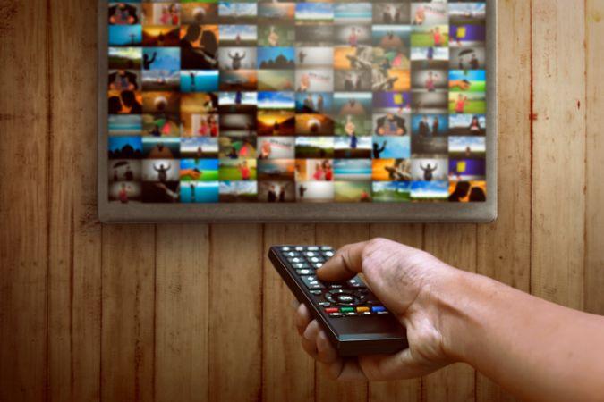 Fernbedienung in der Hand eines Mannes zeigt auf Fernseher mit zahlreichen unterschiedlichen Kacheln unterschiedlicher Filmangebote