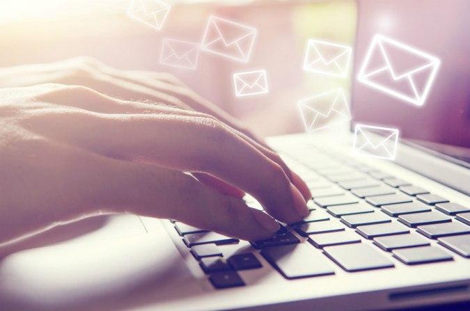 Hand auf Laptoptastatur ausdem Bildschirm fliegen Umschläge bzw. E-Mails