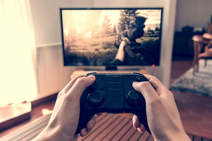 Fernseher mit Ego-Shooter Spiel und im Vordergrund halten zwei Haende einen Controller