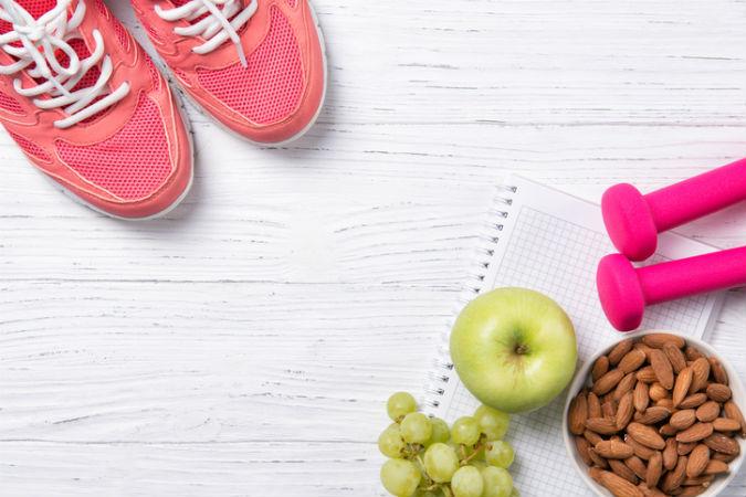Sportschuhe, Obst, Nüsse und Hanteln liegen auf dem Boden