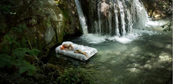 Frau schwimmt mit Matratze neben Wasserfall_neu