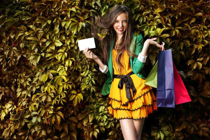 Frau hält Shoppingbags vor Herbstlaub in die Luft