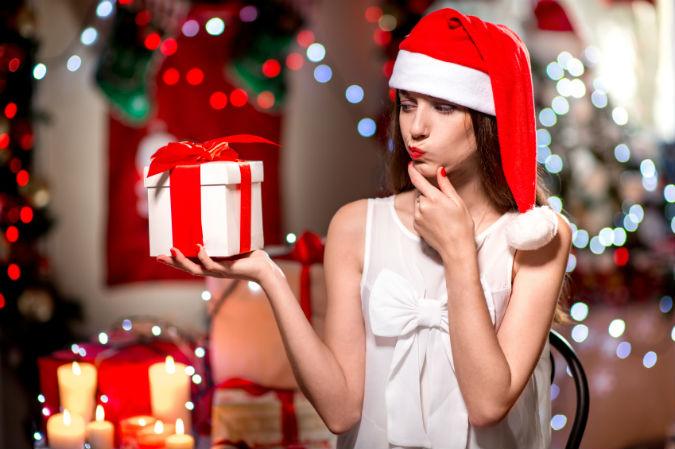 Frau mit Weihnachtsmütze und Geschenk