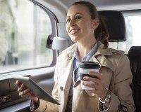 Frau trinkt Kaffee im Auto