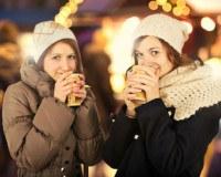 Zwei Frauen stehen mit Glühwein auf einem Fest.
