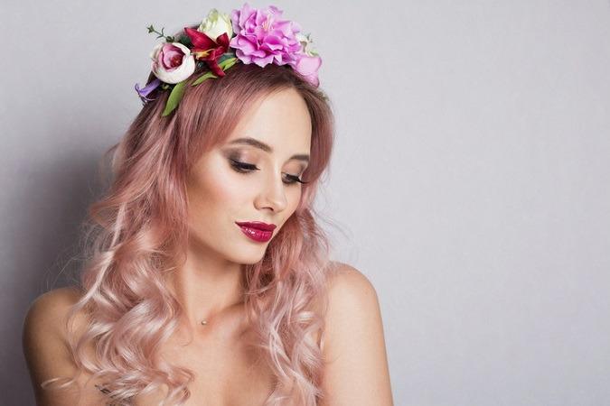 Junge Frau mit langen, Pastellrosa Haaren und Blumenkranz