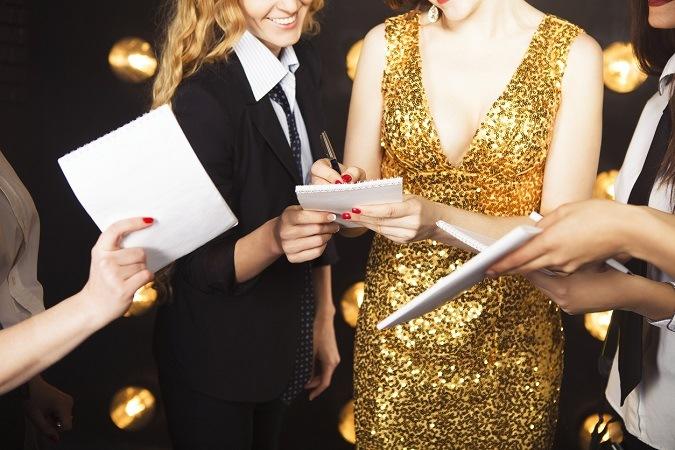 Frau in goldenem Kleid auf dem Roten Teppich gibt Autogramme