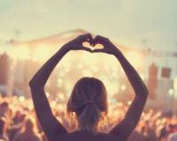 Festivalbesucherin zeigt der Musikbühne ein Herz mit ihren Händen