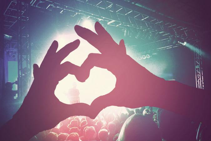 Hände formen auf Konzert ein Herz