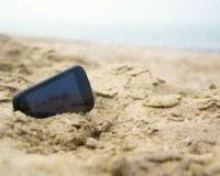 Ein Handy liegt am Strand im Sand.
