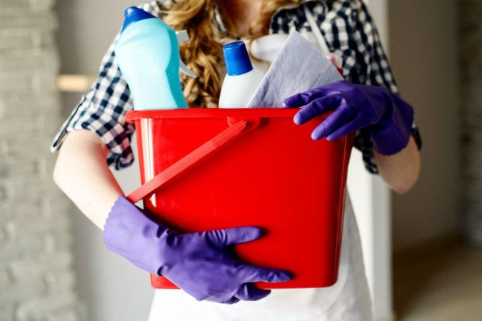Frau mit Putzeimer und Reinigungsmitteln im Arm