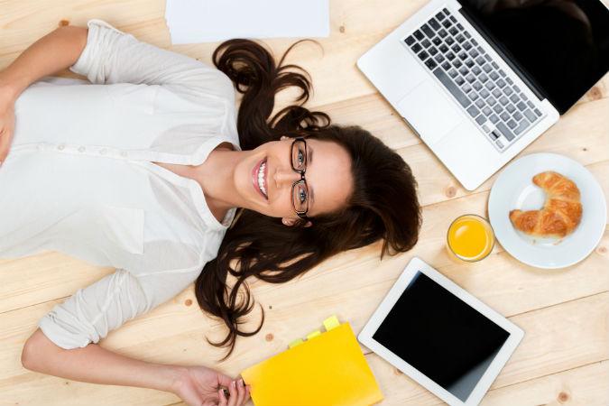 Frau liegt zwischen Office Utensilien