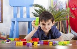 Kleiner Junge spielt mit Legosteinen