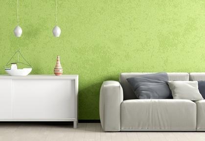 Ein graues Sofa und eine weiße Kommode vor einer grünen Wand.