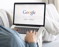 Mann liegt auf dem Sofa und googelt etwas
