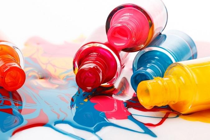 Mehrere bunte, geöffnete Nagellack-Flaschen liegen aufeinander
