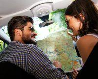 Junges Paar plant seinen Roadtrip mit einer Landkarte, vorn im Fahrzeug sitzend