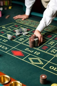 Groupier am Roulette Tisch verschiebt Jetons