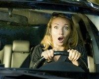 Schockierte Frau beim Auto fahren