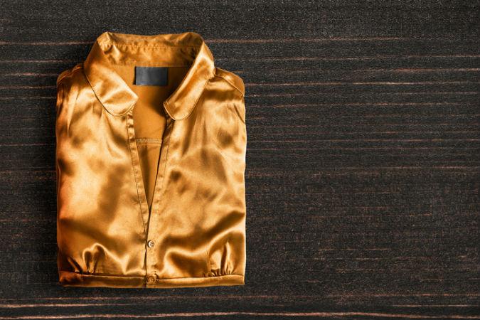 Goldene Bluse auf dunklem Hintergrund