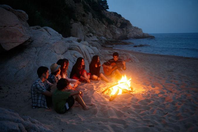 Menschen, die am Strand sitzen und singen