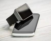 Smartphone und Smartwatch auf einer Holzunterlage
