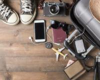Reiseutensielien liegen neben dem Koffer für den Sommerurlaub