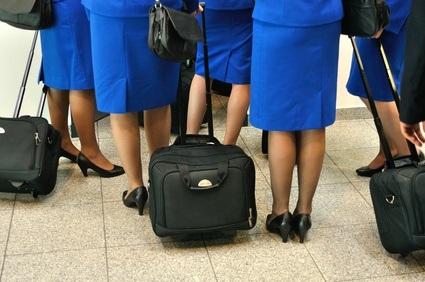 Stewardessen in blau mit Rollkoffer