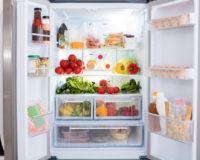Geöffneter Kühlschrank mit Obst und Gemüse gefüllt.