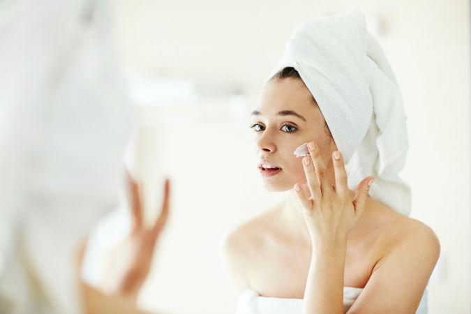 Frau trägt nach dem Duschen Feuchtigkeitscreme im Gesicht auf