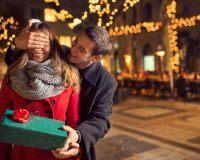 Mann hält Frau von hinten die Augen zu und gibt ihr ein Geschenk