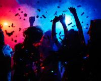 Menschen tanzen im Club in buntem Nebellicht und Konfetti