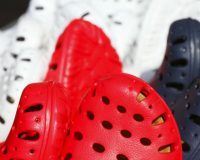 Die Spitzen von vielen Crocs in rot, schwarz und weiß