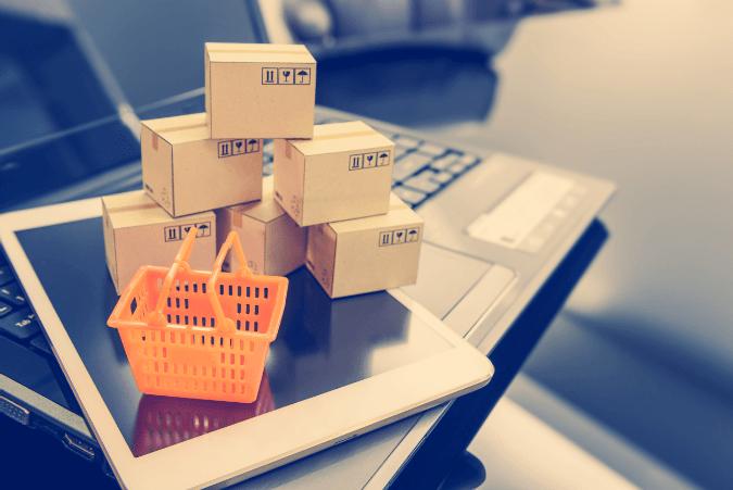 Ein kleiner Einkaufskorb und kleine Kartons auf einem Tablet als Symbol für Online-Shopping