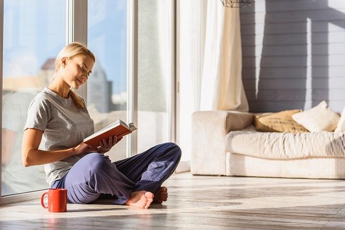 Junge blonde Frau entspannt mit Buch und Kaffee