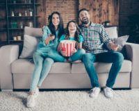 Lachende Familie vor dem Fernseher