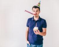 Mann mit Kuchen und Kerze in der Hand