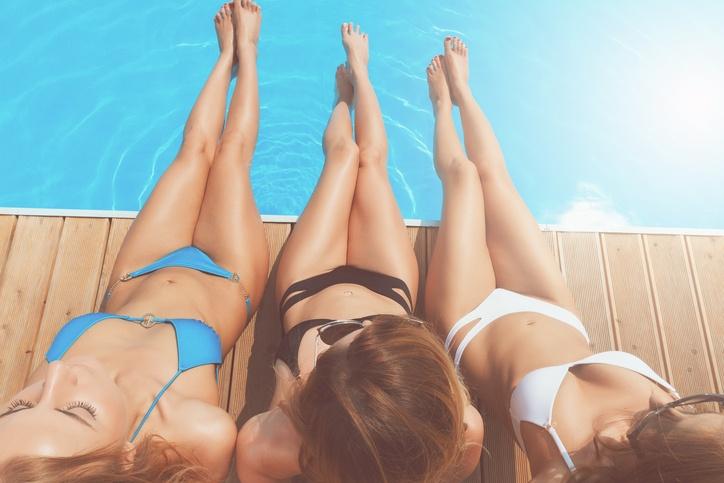 Drei Frauen, die sich am Pool bräunen