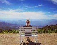 Eine hübsche junge Single-Frau sitzt allein auf einer Bank vor herrlicher Kulisse und genießt offensichtlich die Ruhe