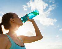 Frau trinkt aus Sportflasche, Himmel im Hintergrund