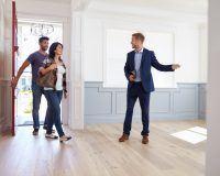 Einem Paar wird eine leerstehende Wohnung vom Makler gezeigt