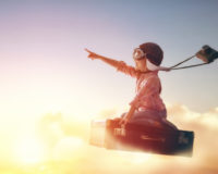 Kind fliegt auf einem Koffer wie in einem Traum