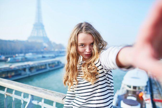 Junge Frau macht ein Selfie mit dem Eiffelturm im Hintergrund