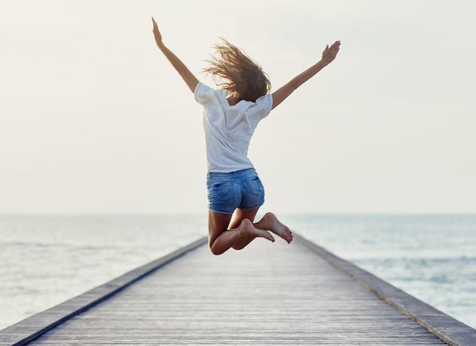 Frau springt in die Luft vor Freude