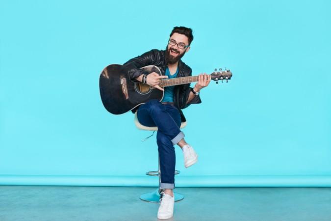 Mann mit Gitarre sitzt auf Stuhl vor blauem Hintergrund