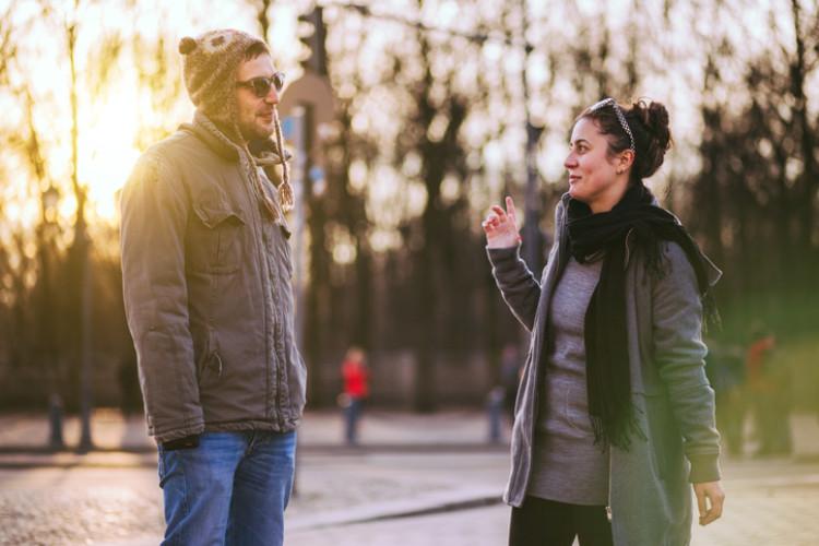 Mann spricht Frau auf Straße an
